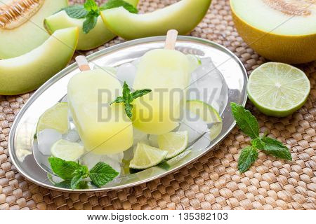 Melon and lime sorbet ice cream on silver plate with ice cubes, lime pieces, mint leaves near melon slices, lime on a straw napkin background. Melon and lime sorbet ice cream popsicles. Horizontal.