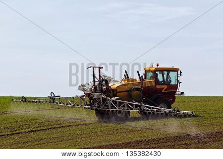 LINSLADE, UK - MAY 5: A crop sprayer applies fungicide to the young cereal plants on a bright spring day on May 5, 2016 in Linslade. The UK grows around 16mn tonnes of wheat per annum