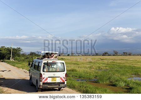 AFRICA, KENYA, MAY, 05, 2016 - Visitors on jeep shoot near Mount Kilimanjaro in Amboseli National Park at Rift Valley Province of Kenya.