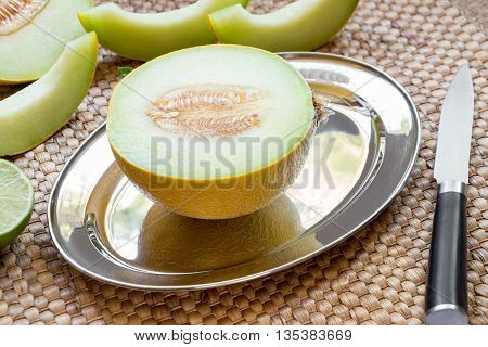 Diagonally at the center on a silver platter half of melon near melon slices, knife on a straw napkin background. Half of melon on silver platter. Horizontal.