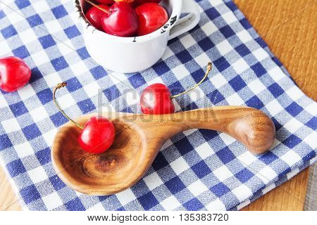 Composition of cup, wooden spoon and berries. Cherries is the reason of the longevity. White retro cup, wooden spoon and berries on a checkered napkin on the table. Wooden handmade spoon with retro cup