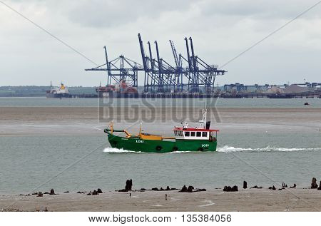 SHEERNESS, UK - JUNE 14: A local fishing boat passes the backdrop of Sheerness docks while heading down the Swale estuary on June 14, 2013 in Sheerness. Kent has approx.131 licensed fishing vessels