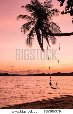 Beautiful sunset over the beach with coconut palm tree and hanging seat