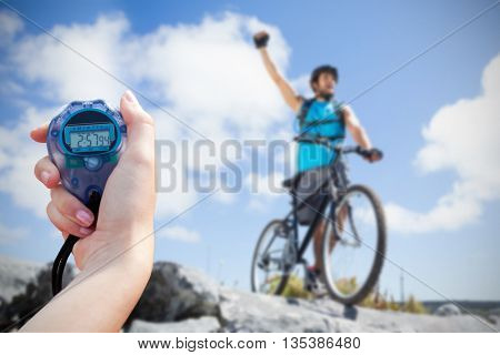 Composite image of close-up of a woman holding a chronometer to measure performance of biker