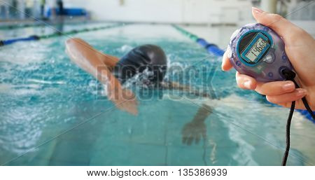 Composite image of a hand holding a timer against fit swimmer doing the front stroke in the swimming pool