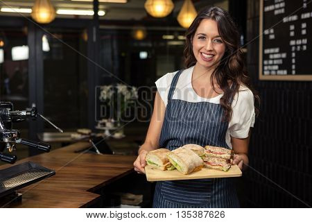 Smiling barista holding plate with sandwich at coffee shop