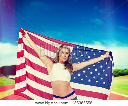Athlete posing with american flag after victory against athletics field on a sunny day