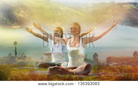 yoga retreat, fitness, sport and lifestyle concept - smiling couple making exercises sitting on mats outdoors, double exposure effect