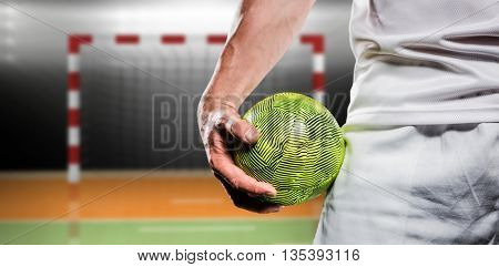 Sportsman holding a ball against digital image of handball goal