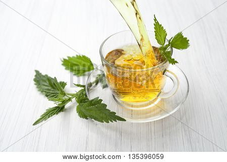herbal tea with nettle on white wood