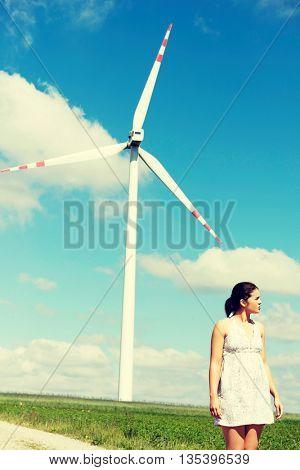 Happy teen girl next to wind turbine.