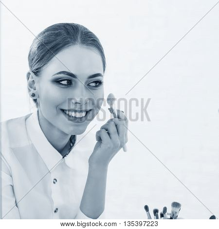 Beauty woman applying makeup. Beautiful girl looking in the mirror and applying cosmetic on the cheekbones.