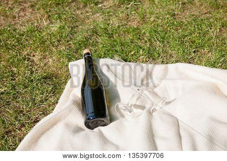 Champagne bottle and glasses on white blanket