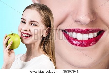 Beautiful young woman with teeth braces holds green apple on the blue background
