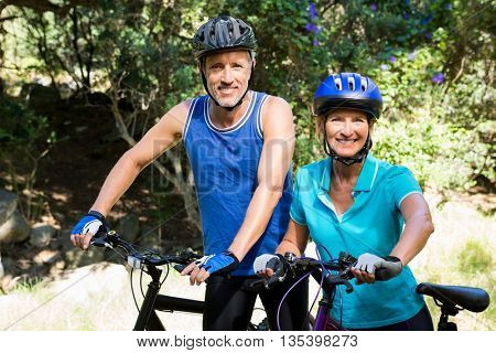 Mature couple posing with their bike on the wood