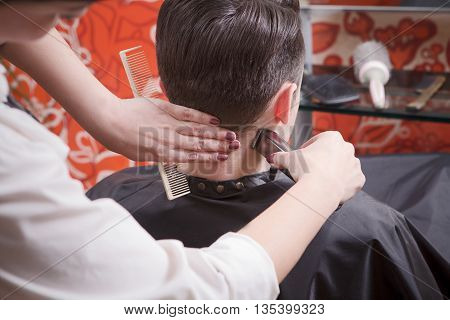 Closeup picture of barber girl using hair clipper for making handsome man' hair cut in hairdressing salon. Hairdresser using hair clipper for hair.