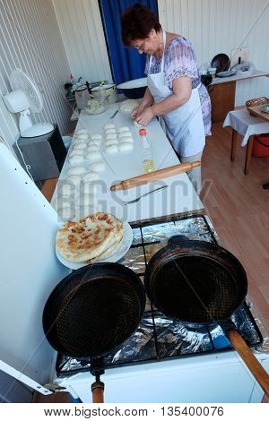 ORADEA, ROMANIA - AUGUST 01, 2015: a middle-aged woman in a makeshift workroom prepares the balls of dough for the preparation of traditional placinta