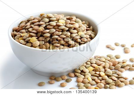 White Ceramic Bowl Of Green Uncooked Lentils Isolated On White In Perspective. Spilled Lentils.
