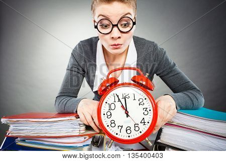Corporate job workaholism time concept. Emotional secretary with clock. Nervous female office worker at desk with alarm ringer.