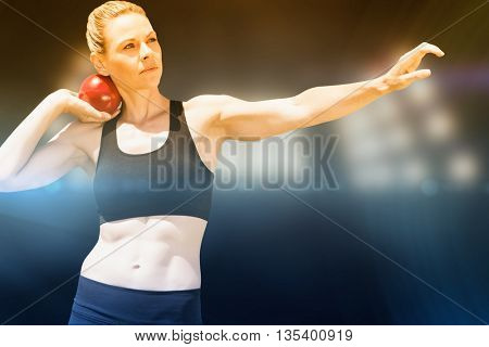 Front view of sportswoman practising shot put against composite image of spotlight
