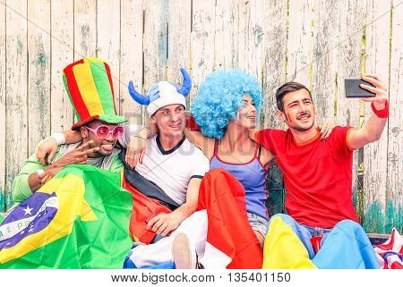 Group of mixed supporter taking selfie outside football stadium - Football fans self photo against violence and unrest at sports event - Concept of friendship and fun together -
