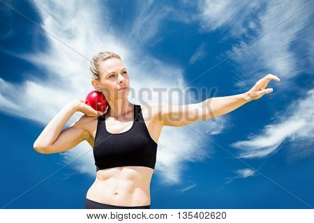 Front view of sportswoman practising shot put against blue sky with clouds