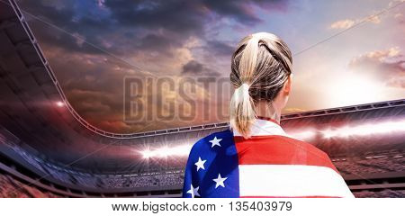 Rear view of american sportswoman is posing against composite image of stadium with cloudy sky