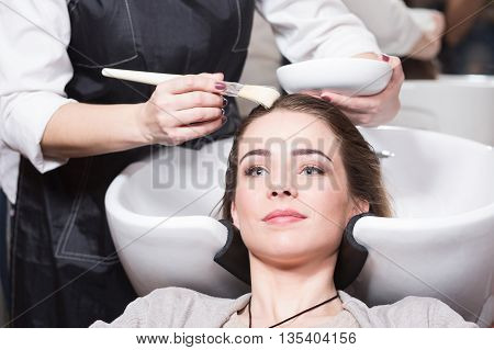 Beautiful lady having her hair washed by hairdresser in hairdressing salon. Barber girl combing her hair in beauty salon.