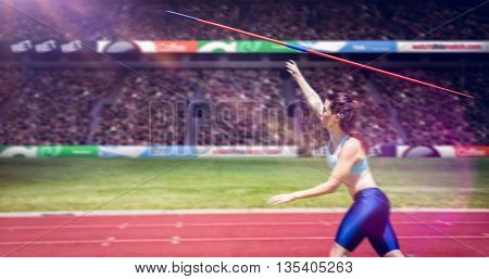 Profile view of sportswoman is practising javelin throw against view of a stadium