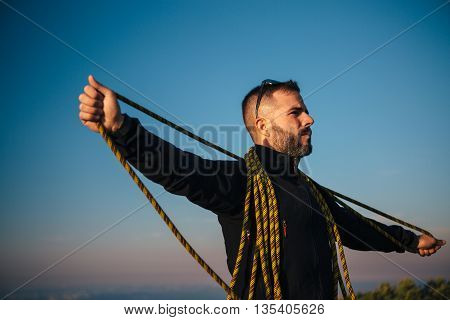 Portrait of adult traveler holding rope in widened arms