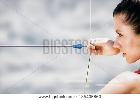 Close up of sportswoman practising archery on a white background against cloudy sky