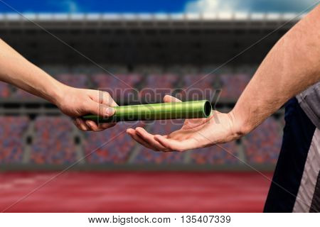 Man passing the baton to partner on track against athletic field on a stadium