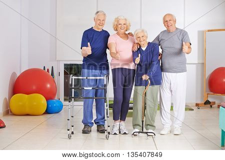 Happy group of senior people holding thumbs up together in physiotherapy