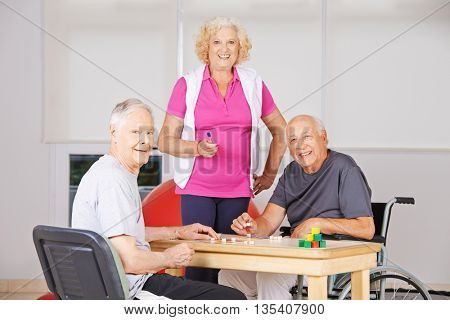 Three happy senior citizens playing Bingo together in a nursing home