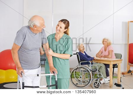 Old man standing with geratric nurse in nursing home with senior people