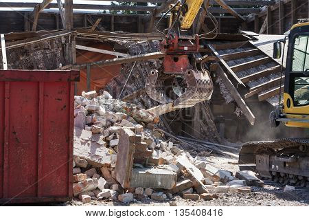 Demolition rubble and an almost demolished house in the background