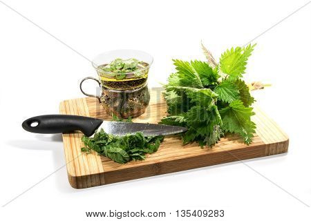 bunch of fresh nettle kitchen knife sliced leaves and a cup with nettle tea on a cutting board isolated with shadows on a white background selected focus narrow depth of field