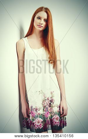 Tender portrait of beautiful redhead female wearing sleeveless flower print summer dress posing leaning against white wall. Tonned image poster