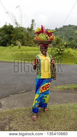 st.Georges Grenada-November 27 2015: old afro american woman with smiling face selling fruits in basket on head and beads