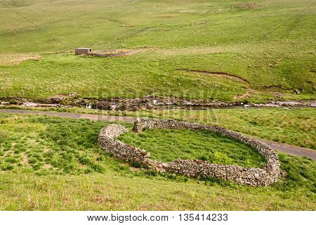 Sheepfold in Upper Coquetdale, the River Coquet winding its way through the Coquetdale Valley past many circular sheepfolds, protection in the harsh winters for hill sheep