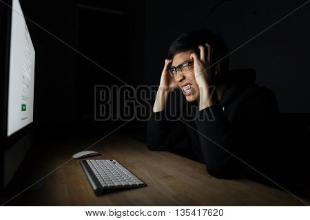 Mad irritated asian young man working with computer in dark room