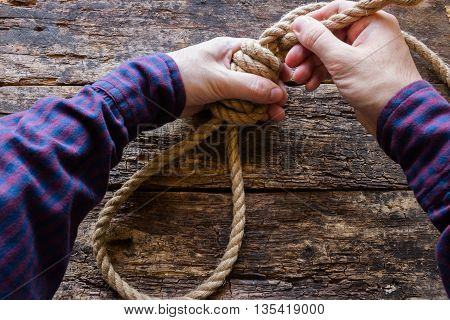 man tying a slipknot on a wooden background