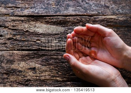 Widow Holding Her Husband's Ring On A Wooden Background