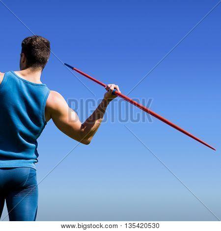 Rear view of sportsman practising javelin throw against bright blue sky