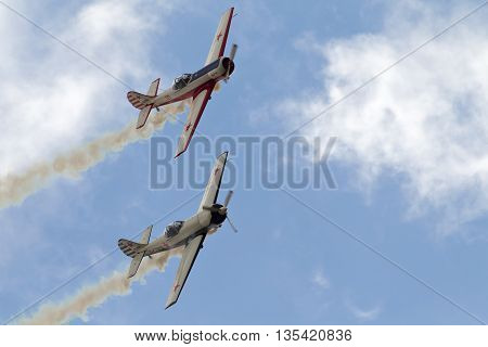 NORTHILL, UK - JULY 5: A pair of vintage Russian built Yak aircraft give an aerial aerobatics display to the crowd below inside Old Warden aerodrome on July 5, 2015 in Northill