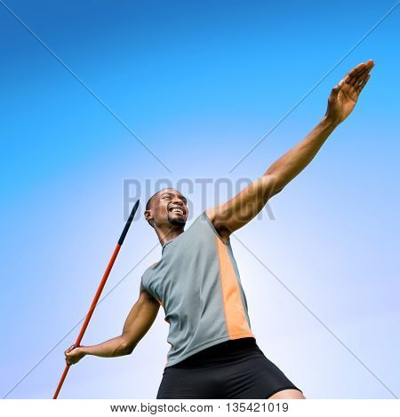 Low angle view of sportsman practising javelin throw against blue sky