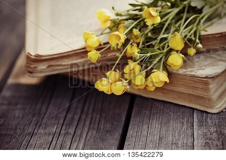 Old open books and bouquet of yellow buttercups on a wooden table.