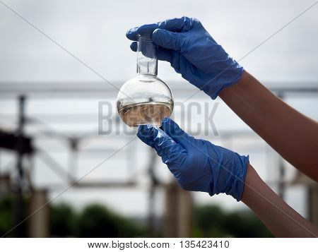 Hand in glove holding a retort with muddy water. Background sky. or power plant construction