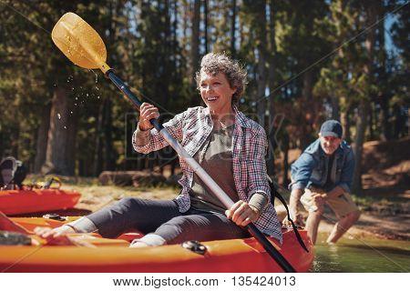 Mature Couple Enjoying A Day At The Lake With Kayaking