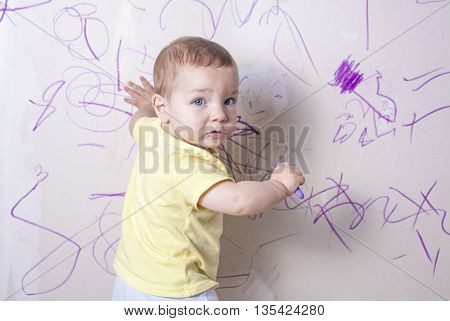 Baby boy drawing with wax crayon on plasterboard wall. He is looking to the camera